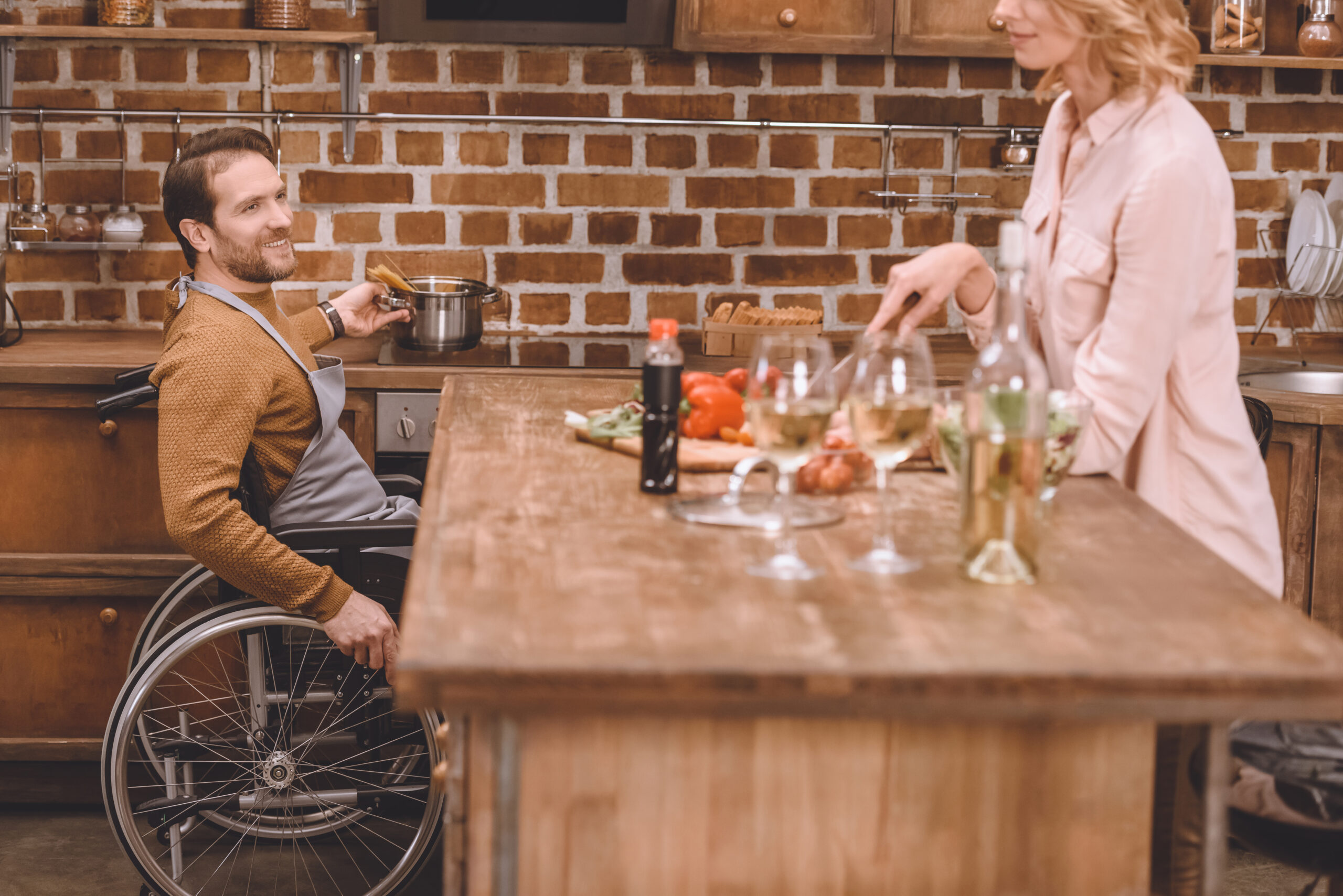 image of a man in a wheelchair helping his wife cook